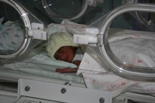 Baby in bonnet in neo-natal unit