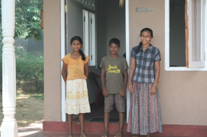 Kaliyani and her children outside their new house