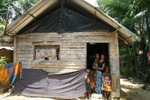 Anusha and her husband Anura have three small children. Their house is made of wooden planks and leaks when it rains. They use plastic sheeting to try and make it a little more water tight.