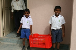 Grade 2 boys collecting lunch boxes from the kitchen