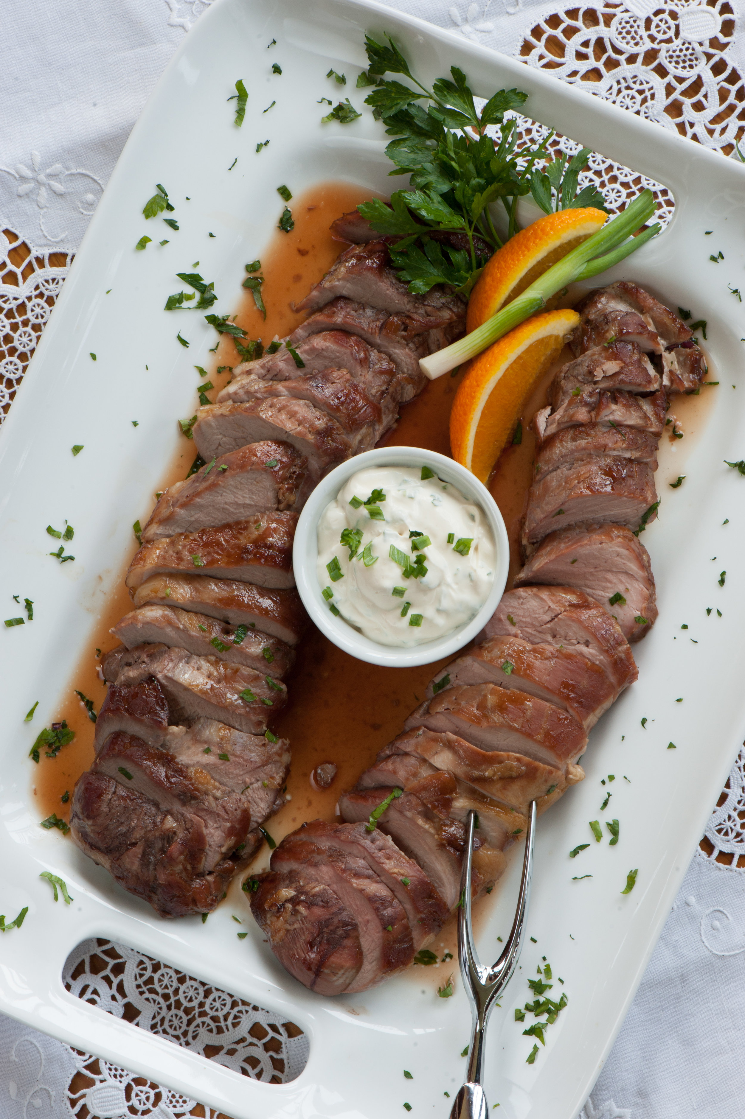 Pork Tenderloin with Scallion Sauce. - Serves 6 to 8Marinade1 pork tenderloin (3 pounds)1/4 cup soy sauce1/4 cup bourbon2 tablespoons brown sugarGreen Onion Sauce2/3 cup sour cream2/3 cup mayonnaise1 tablespoon ground mustard seed2 to 3 green onions, finely choppedCombine marinade ingredients and stir to dissolve sugar. Pur into a Ziploc freezer bag. Place tenderloin in bag and remove air so marinade covers entire tenderloin. Place in a pan and refrigerate for several hours or overnight.Preheat oven to 325 degrees F.Remove tenderloin from marinade. Place on rack in a shallow roasting pan and cook for approximately 45 minutes or until a meat thermometer reads 160 degrees F.Allow to rest for 10 minutes before slicing. Serve with Green Onion Sauce.For the Green Onion Sauce: Combine all ingredients in a small bowl. Cover and refrigerate for several hours before serving to allow flavors to develop.