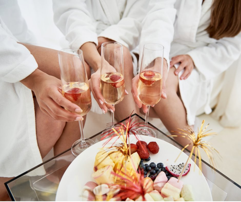 girls-in-bathrobes-holding-glasses-of-champagne-with-strawberries-picture-id1029862122.jpg