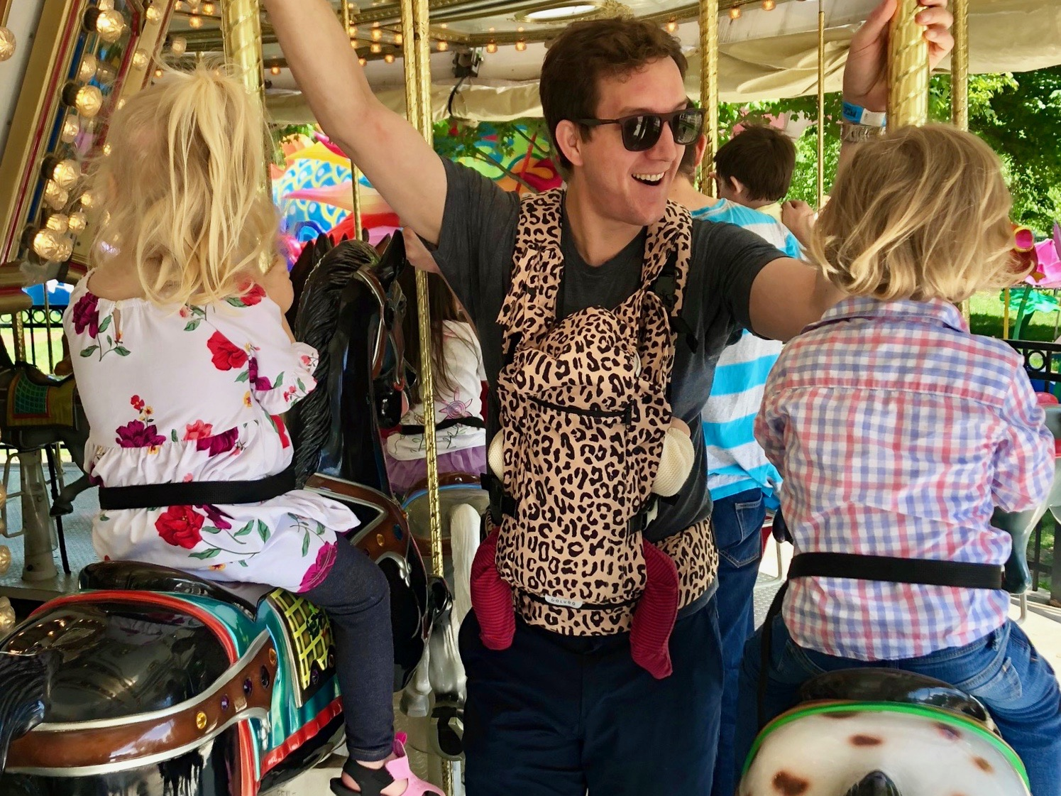 Ted has twins:  And a baby. So he's a Philly family travel expert, whether he likes it or not. Here his kiddos Fritz, Lark, and baby Win—sporting the Colugo Carrier in the  Wild Child  print—are riding the carousel in Franklin Square.
