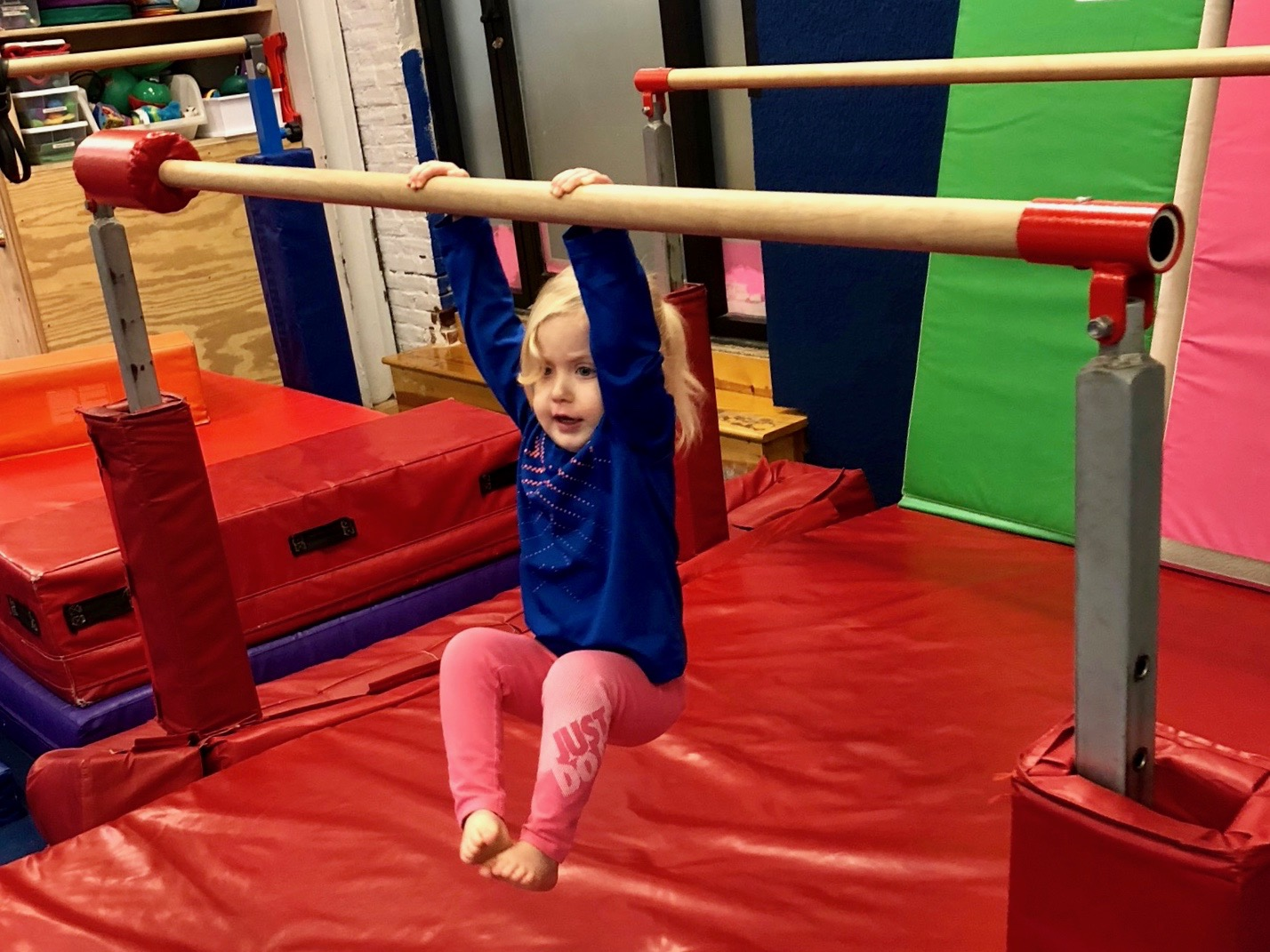 Wonder Woman:  On rainy days, the Iobst family heads to  InMovement  to tumble off some pre-nap energy. Here, Lark hangs from the center's balance beams.