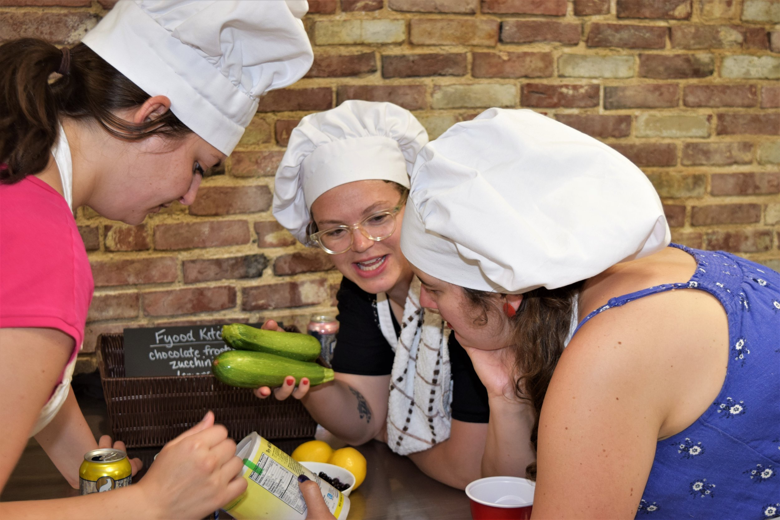 Women brainstorming dish with zucchini and chocolate frosting