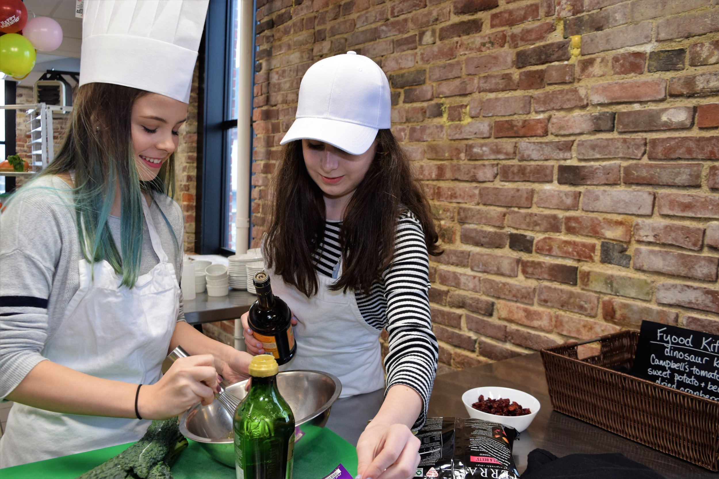 Teen girls birthday party cooking in professional kitchen