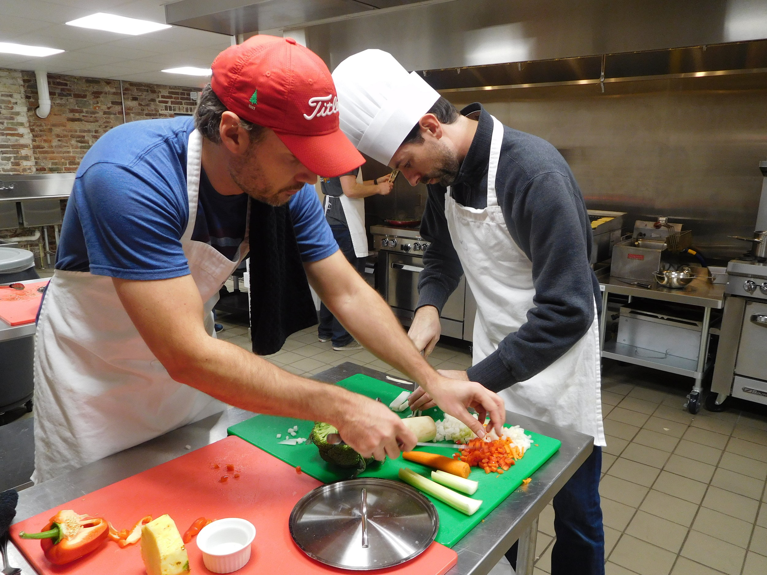 Men chopping vegetables at amateur cooking competition party