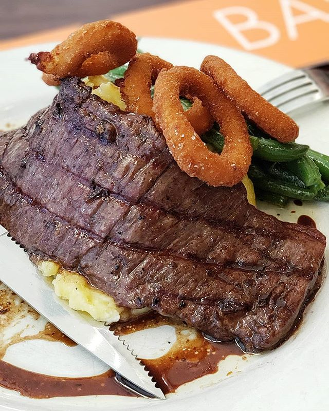 Our Skirt Steak Balsalmico is solid on it's own, but with onion rings on top? NEXT LEVEL! 🔪🥩 Find it served with goat cheese mash and green beans on our dinner menu seven nights a week and taste it for yourself! #dinnergoals #meateater #steakrestaurant