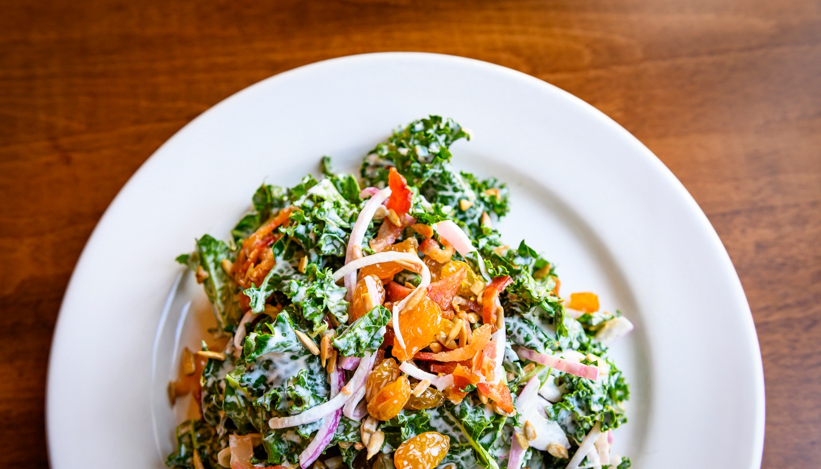 Marinated Kale Slad with toasted Sunflower Seeds, golden raisins, Applewood smoked bacon, red onions, champagne dressing