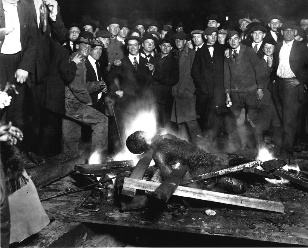 The scene of White on-lookers standing behind Will Brown's burnt body – September 28, 1919