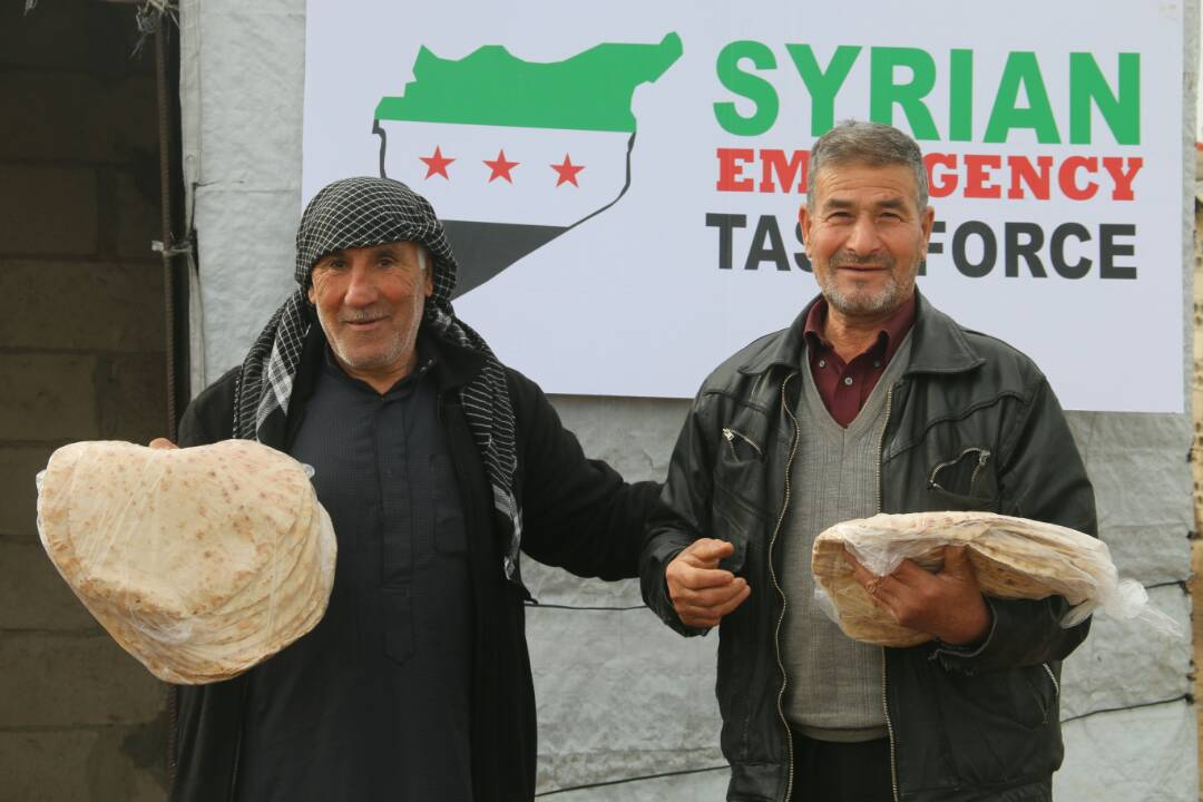 Syrian civilians smiling after receiving bread. SETF provides thousands of internaly displaced families with bread on a monthly basis