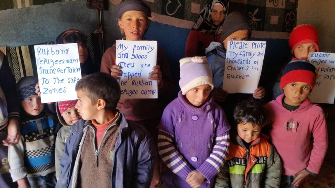 Kids in Rukban hold signs pleading for protection