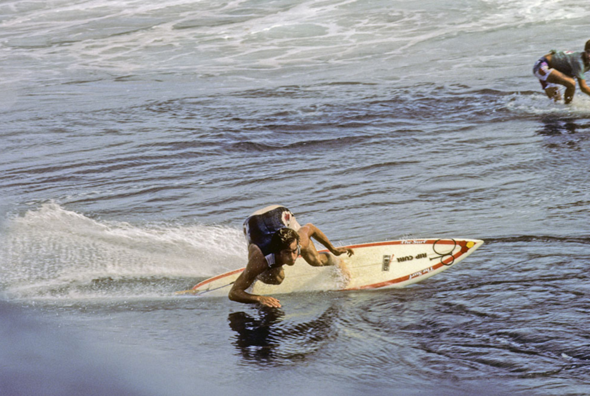 A classic look at Tom Curren's bottom turn from the top. Note his hands, knees, and how low he gets.