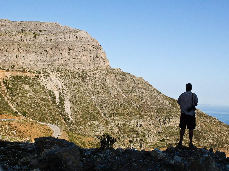 Man overlooking cliffs, Ikaria Island, Greece.