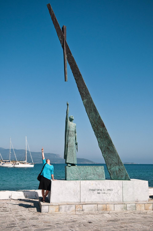 Woman standing next to a statue celebrating Pythagoras, Pythagoreio village, Samos Island, Greece.