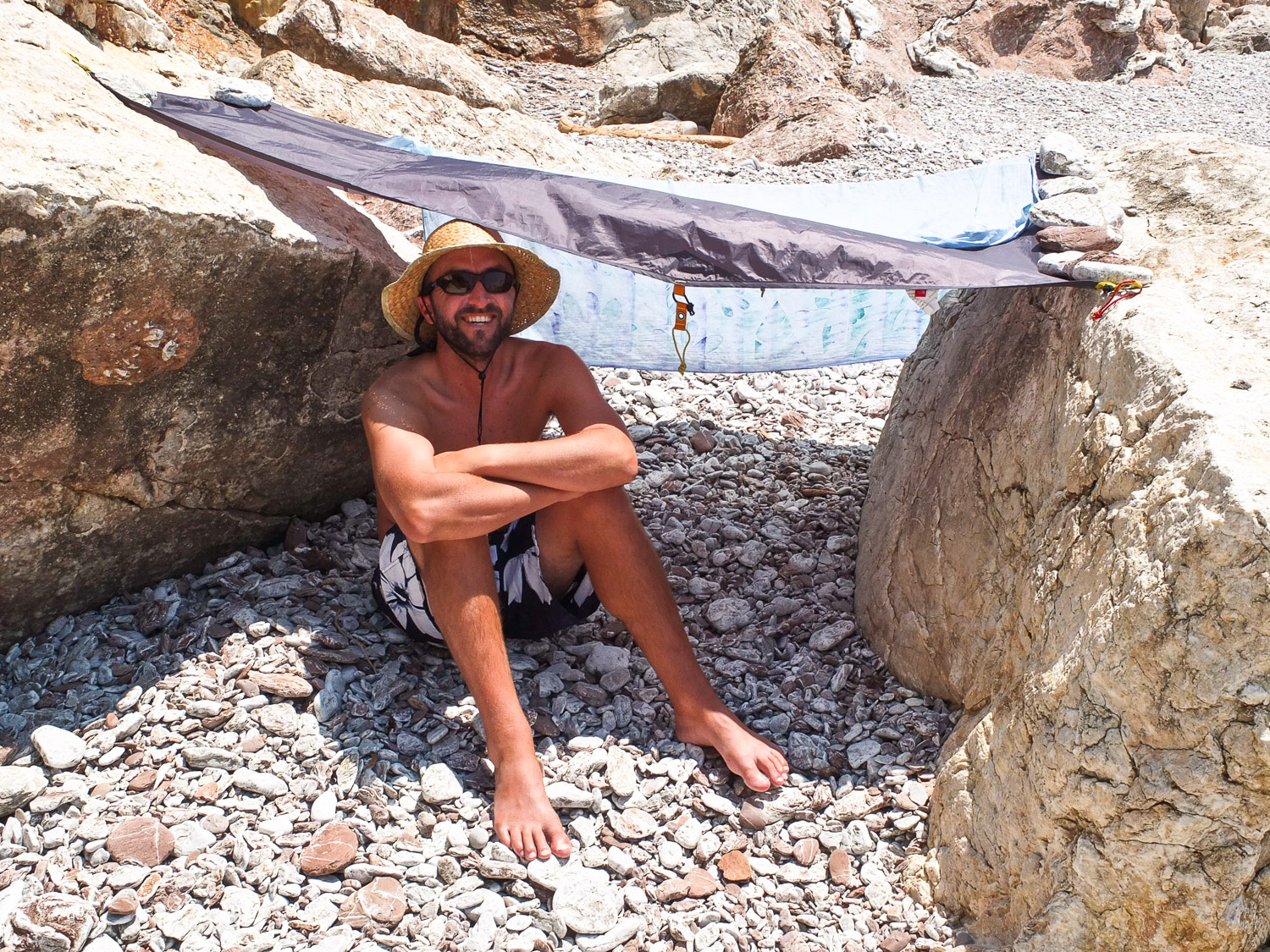 Man sheltering under a tarp, during a sea kayaking trip along the Turquoise Coast, Turkey.