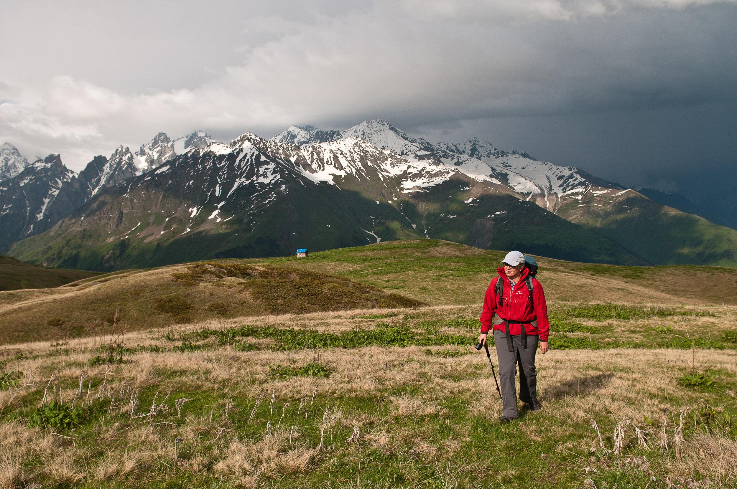 Woman trekking amongst mountains, Mestia, Georgia.