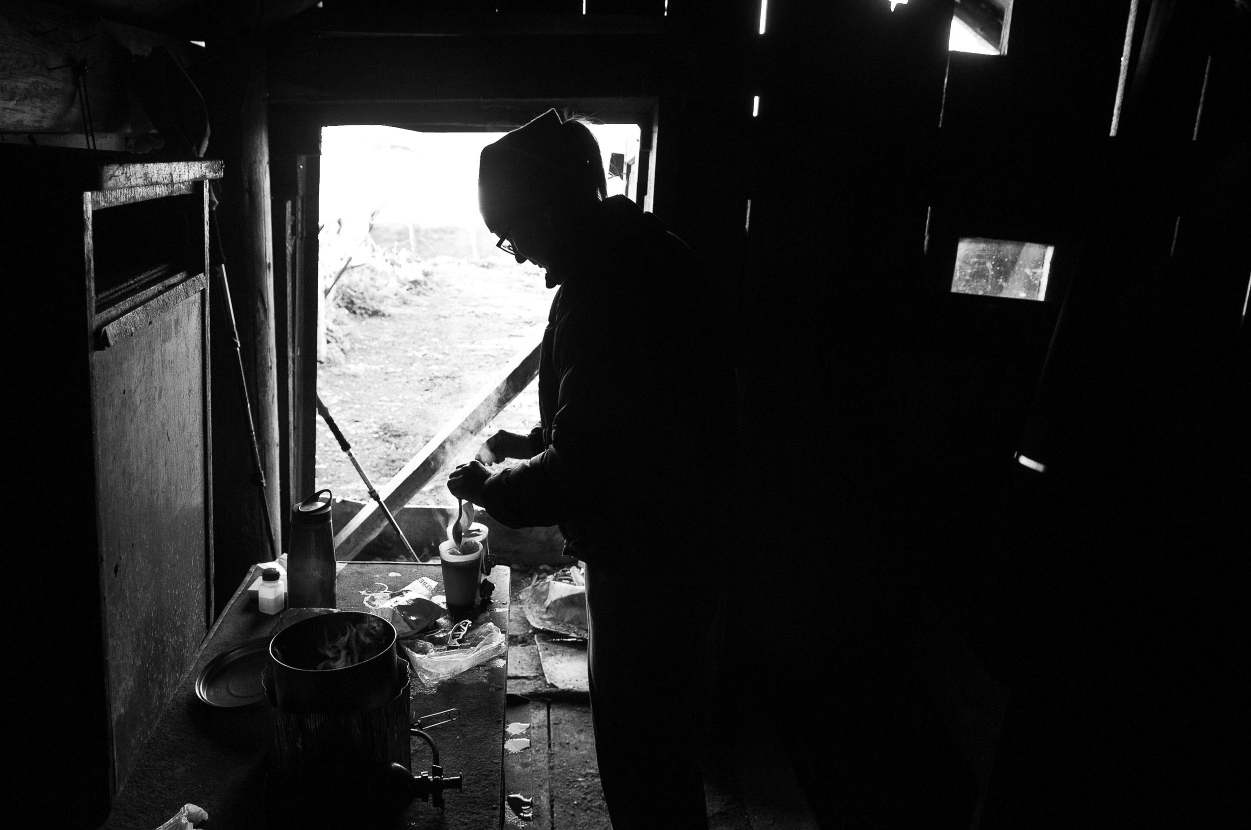 Woman making tea in an old mountain hut, Mestia, Georgia.