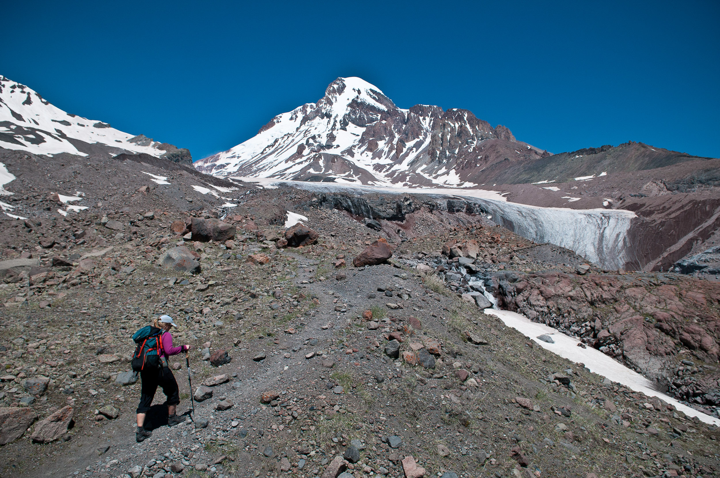Trekker approaching Kazbegi mountain, Georgia.