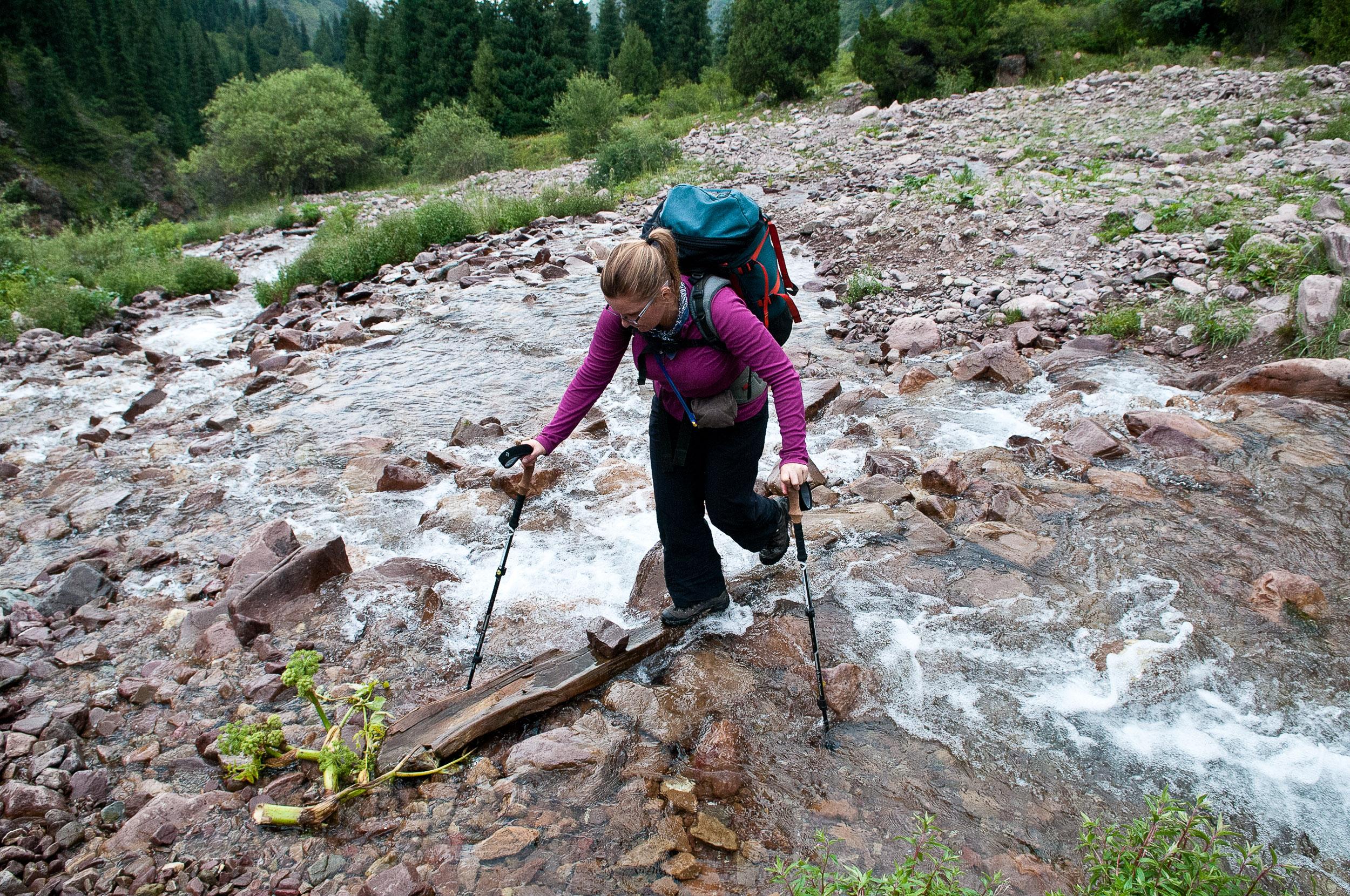 Woman crossing a creek, Kyrgyzstan.