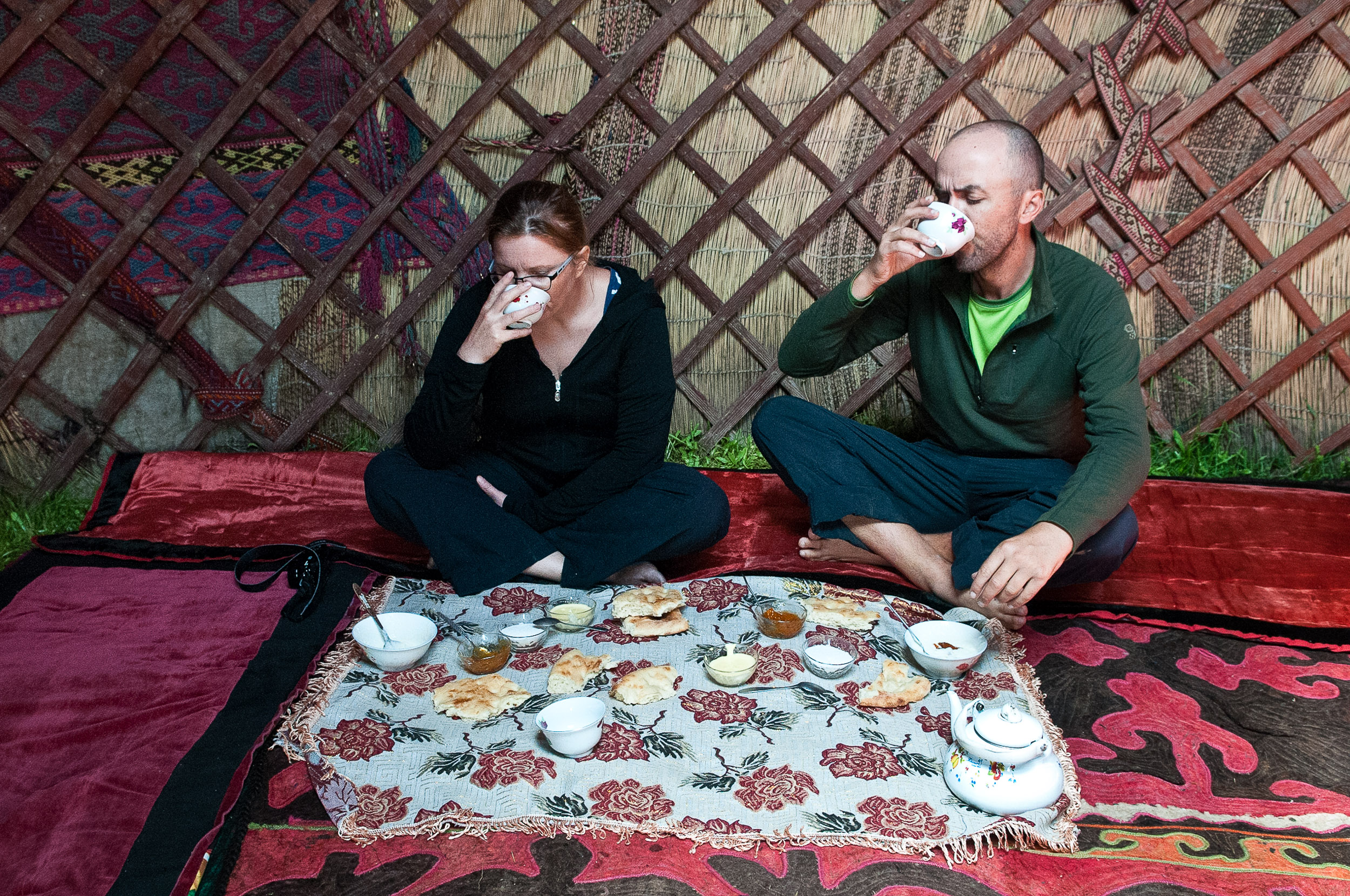 Jane and Thomas eating typical Kyrgyzstan food inside a yurt, Kyrgyzstan.