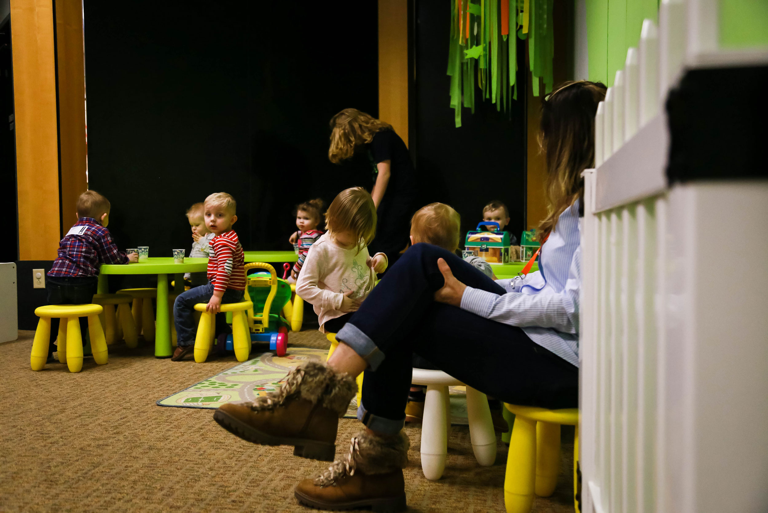 Toddlers play at activity tables as volunteers assist