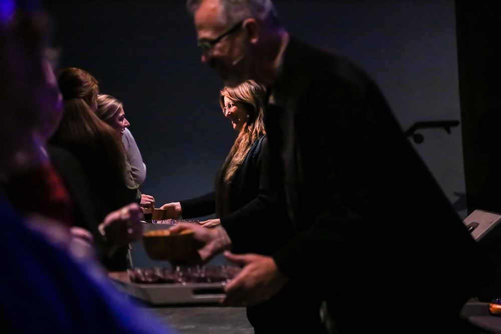 Pastors Joe and Janice Wood serve communion as they speak blessings over the congregation