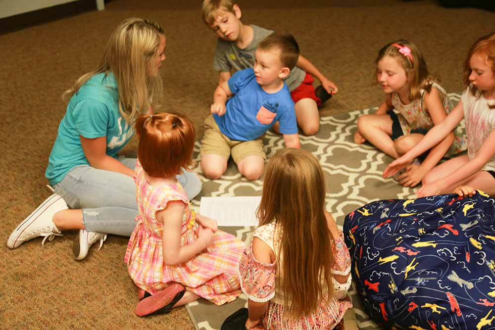 V-Kids instructor sits on floor engaging elementary kids with a Bible story