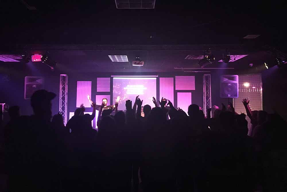 Large group of middle and high school students fill the Wednesday night Reckless Student Ministry space as they lift their hands in worship