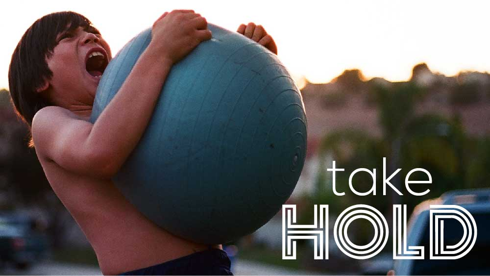 Shirtless boy grasping a playground ball and yelling. 'Take Hold' is written below.