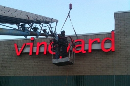 Man in boom lift installs the Vineyard Neon sign