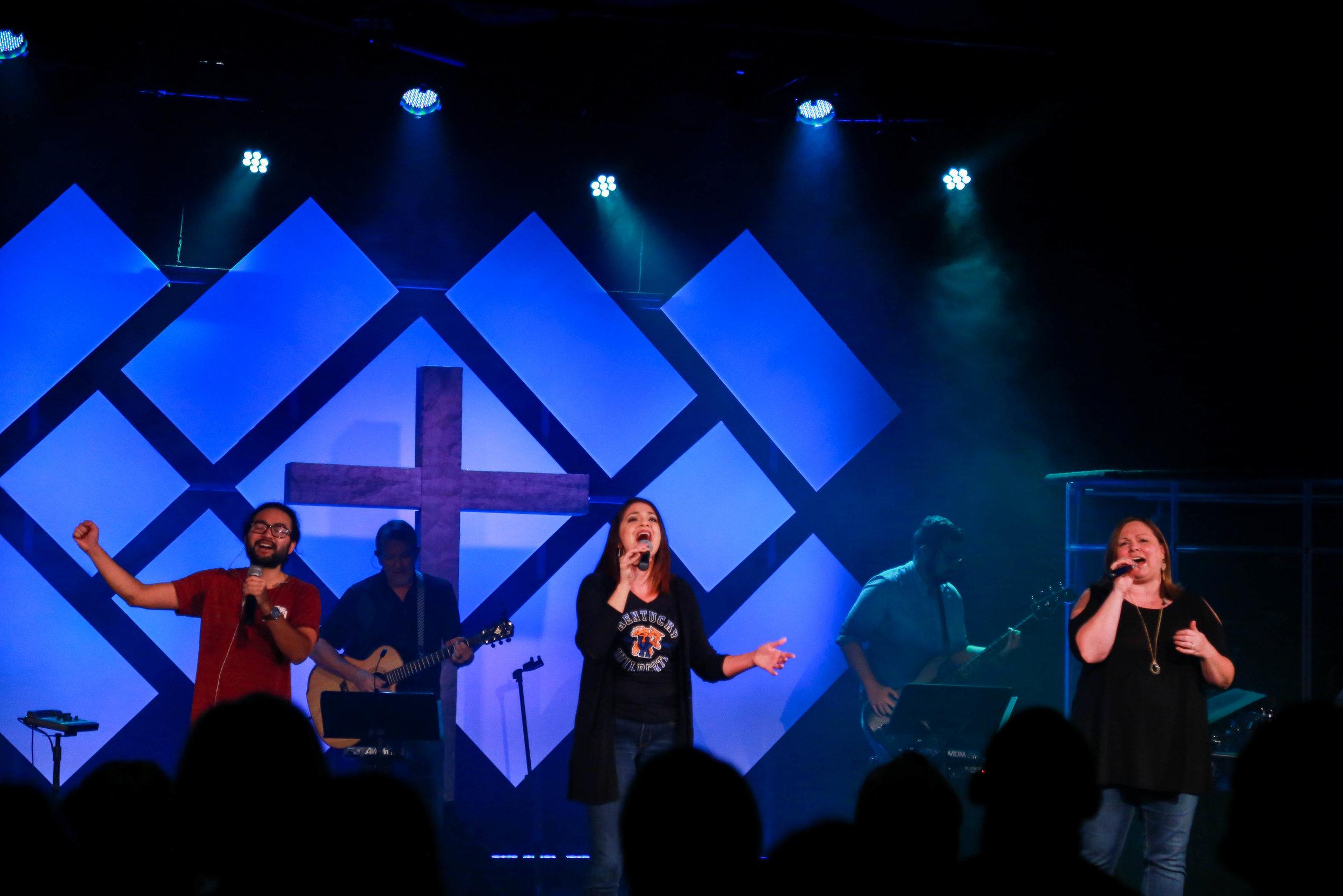 Three vocalists sing on stage at Vineyard Richmond
