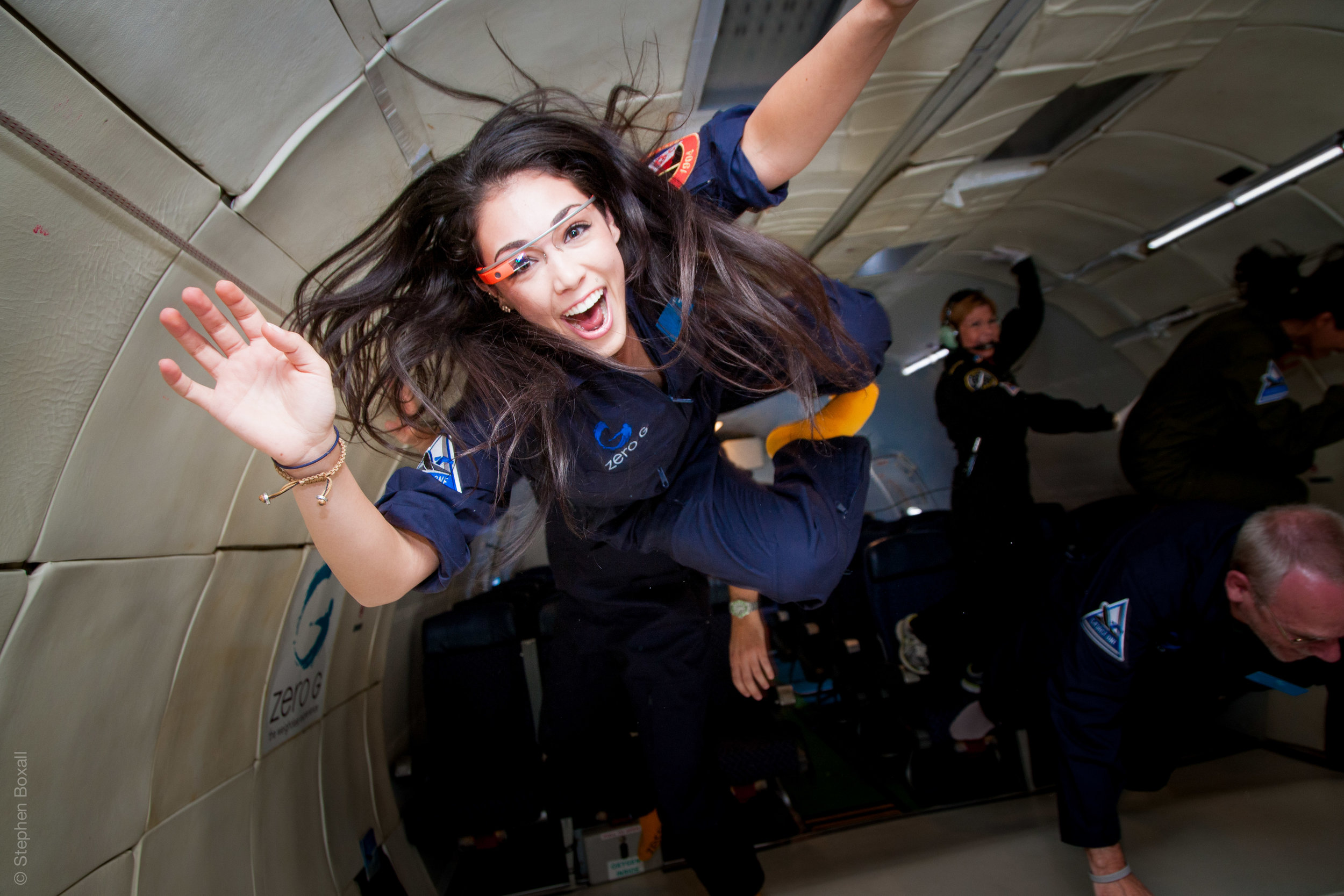 Kellie Gerardi is smiling at the camera and floating in zero gravity. She has long dark brown/black hair and is wearing a navy blue, Zero G jumpsuit and smart glasses.