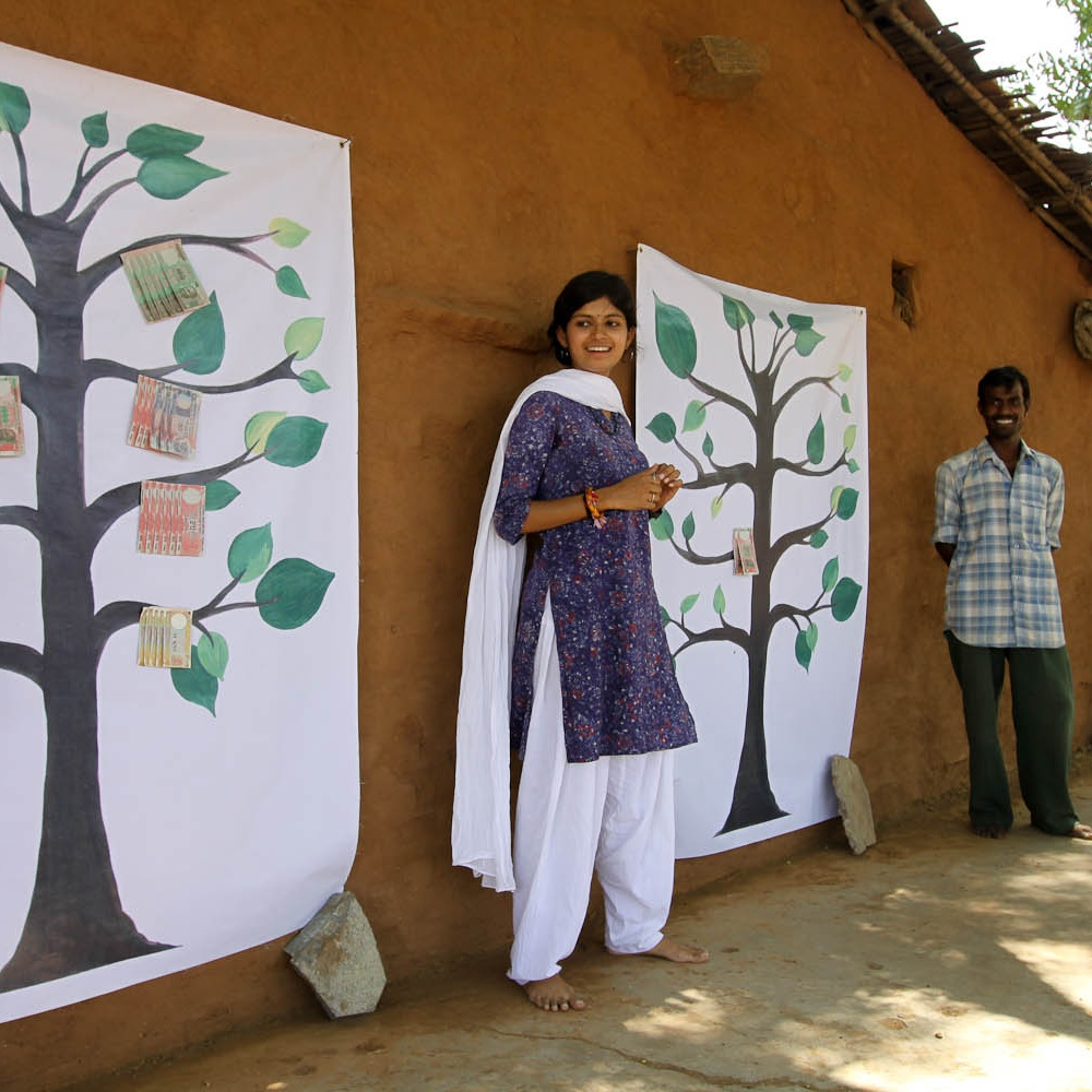 Rupal Kulkarni is standing outside in front of a wall with paintings of money trees hanging on it. She has black hair and is wearing a dark purple top with white pants and a white scarf.