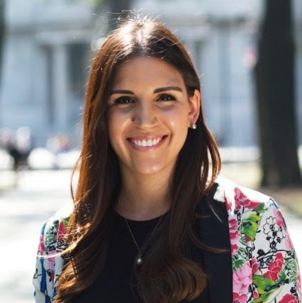 Andrea Garcia Lopez stands outside in the sun, smiling at the camera. She has long brown hair and is wearing a black shirt underneath a floral patterned jacket.