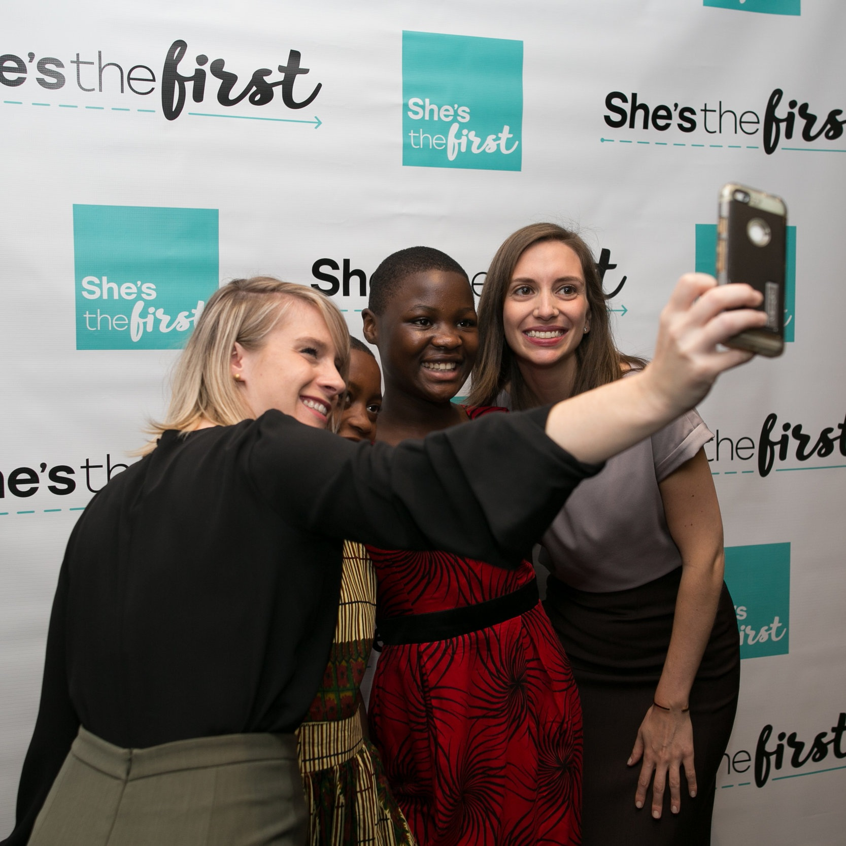 "Christen Brandt and Tammy Tibbetts stand smiling with two other women, taking a group selfie in front of a backdrop that reads: ""She's the first."""