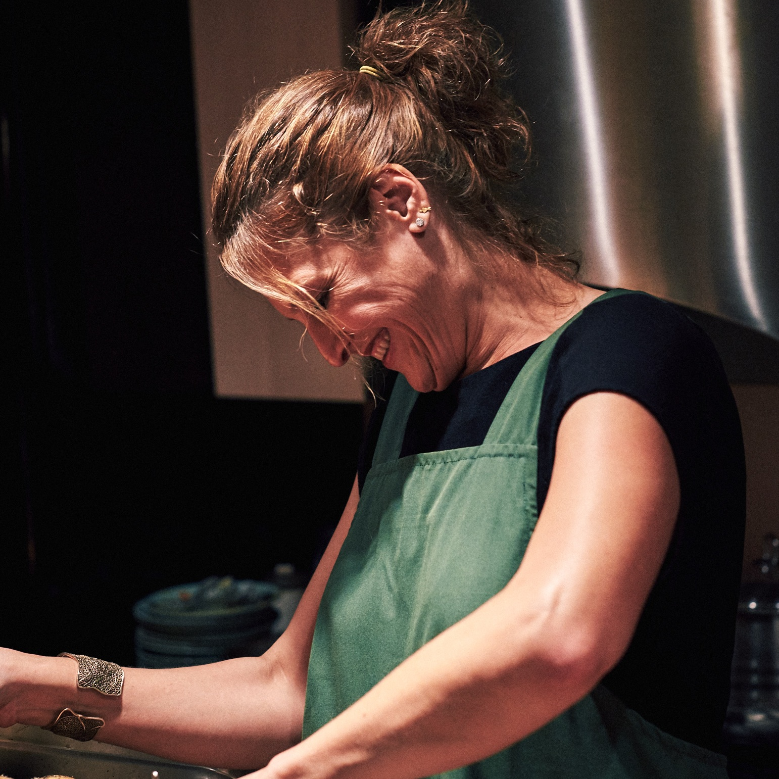 Hannah Goldberg is smiling in profile. Her brown hair is in a ponytail and she is wearing a green apron over a black t-shirt.