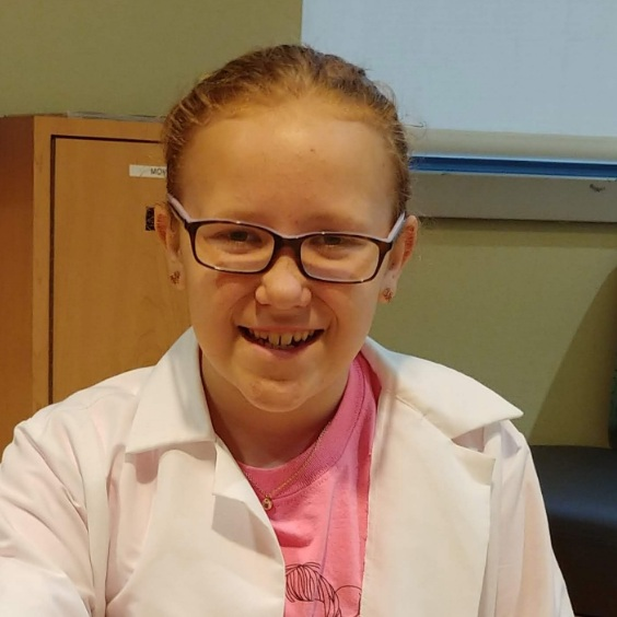 Lexi Flanders sits smiling at the camera. Her blond hair is pulled back and she is wearing glasses, a pink t-shirt and a white lab coat.