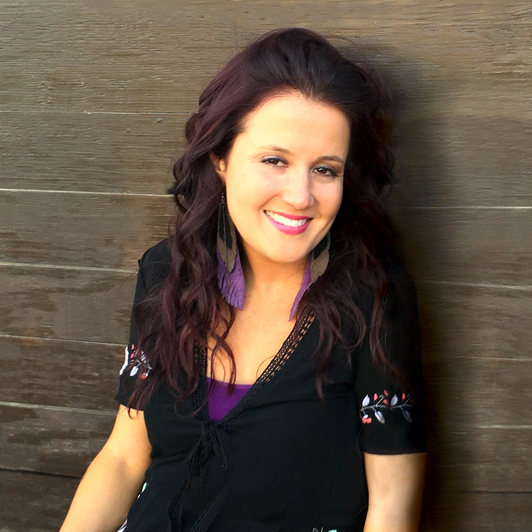 Amirose Eisenbach sits against a wooden wall, smiling at the camera. She has long, wavy dark hair and is wearing a black v-neck top with a purple shirt underneath.