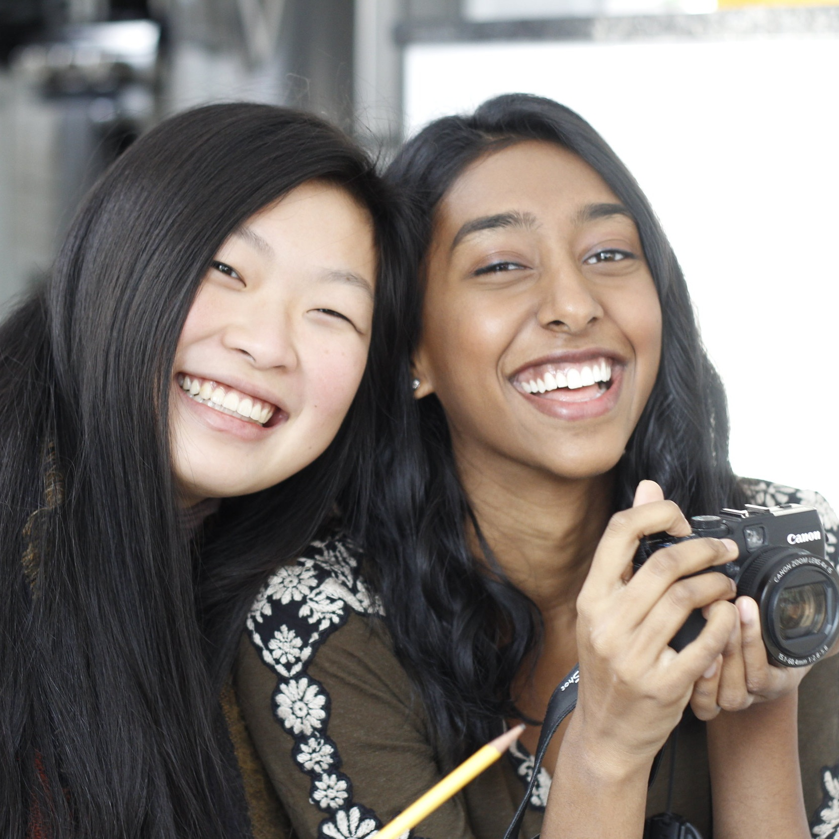 Priya Vulchi and Winona Guo are smiling at the camera. They both have long black hair and one of them is holding a camera.
