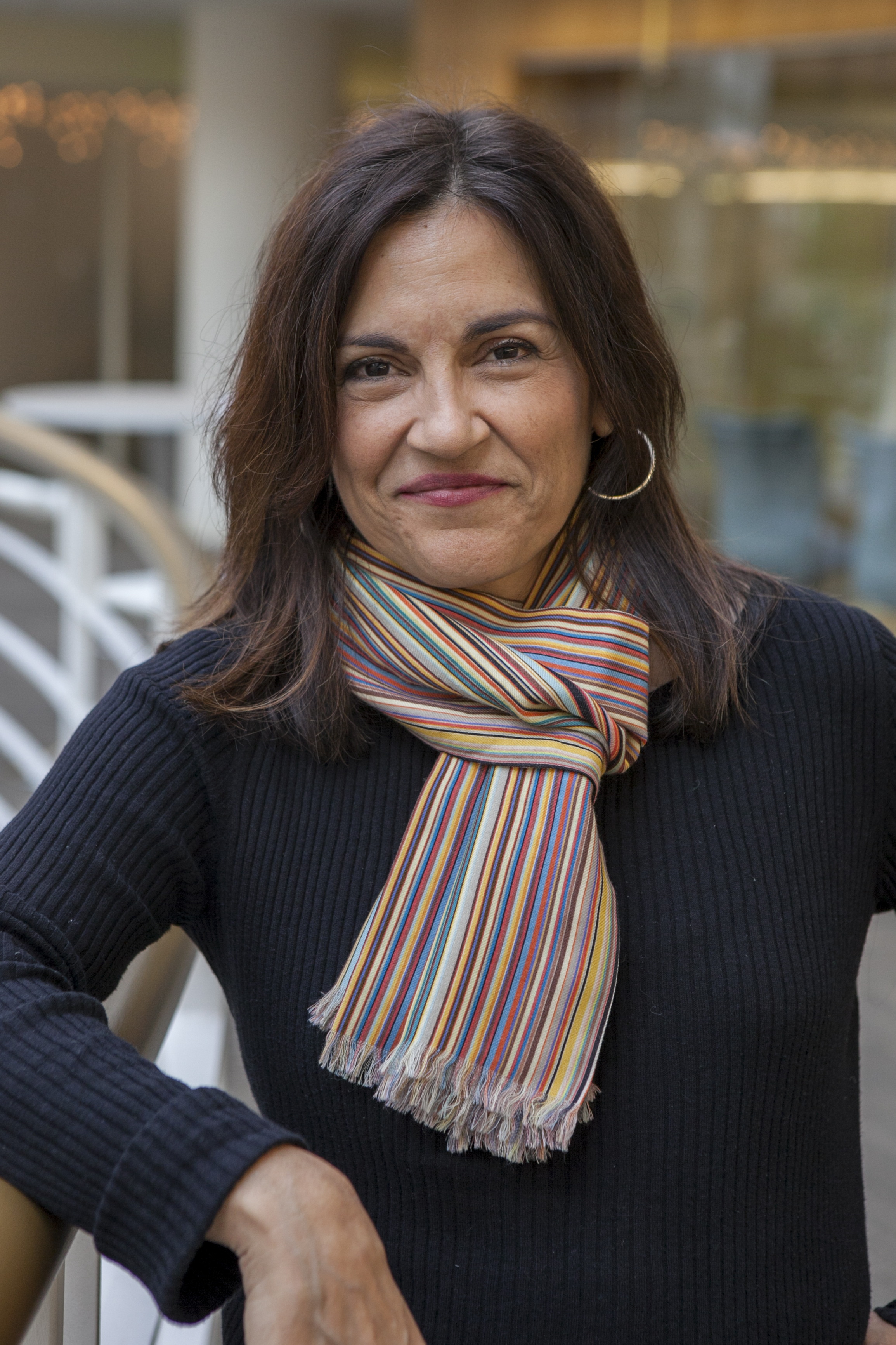 Yalda T. Uhls stands smiling at the camera. She has medium length brown hair and is wearing a navy blue sweater with a colorful striped scarf.