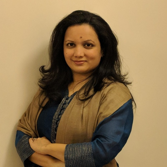 Neha Barjatya stands smiling at the camera. She has medium length black hair and is wearing a dark blue and tan blouse.