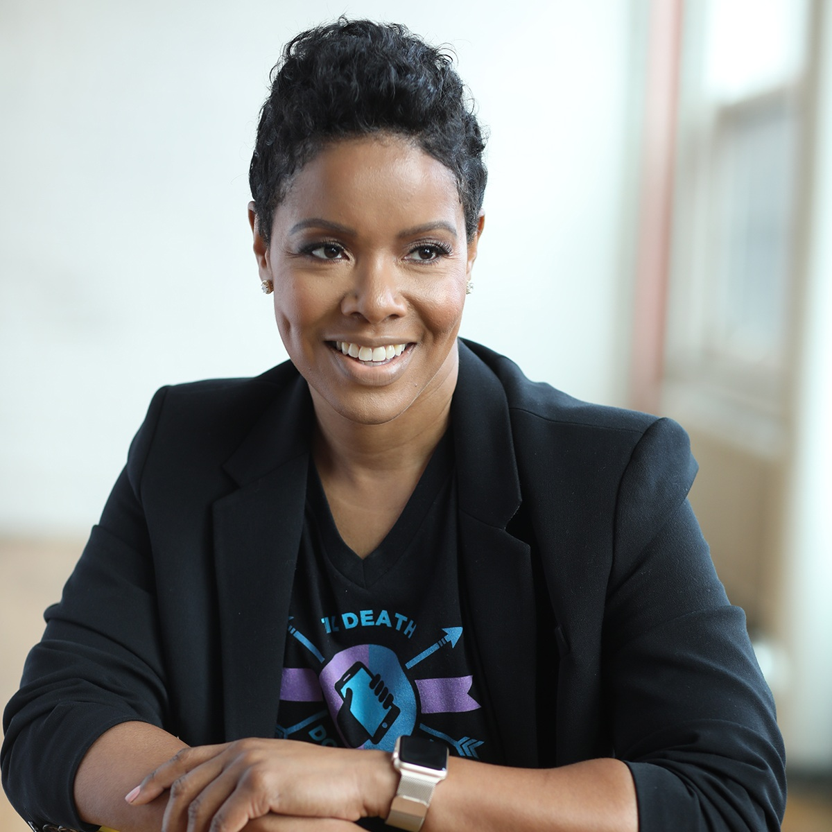 Stephanie Humphrey sits smiling at the camera. She has short black hair and is wearing a black blazer over a black t-shirt.