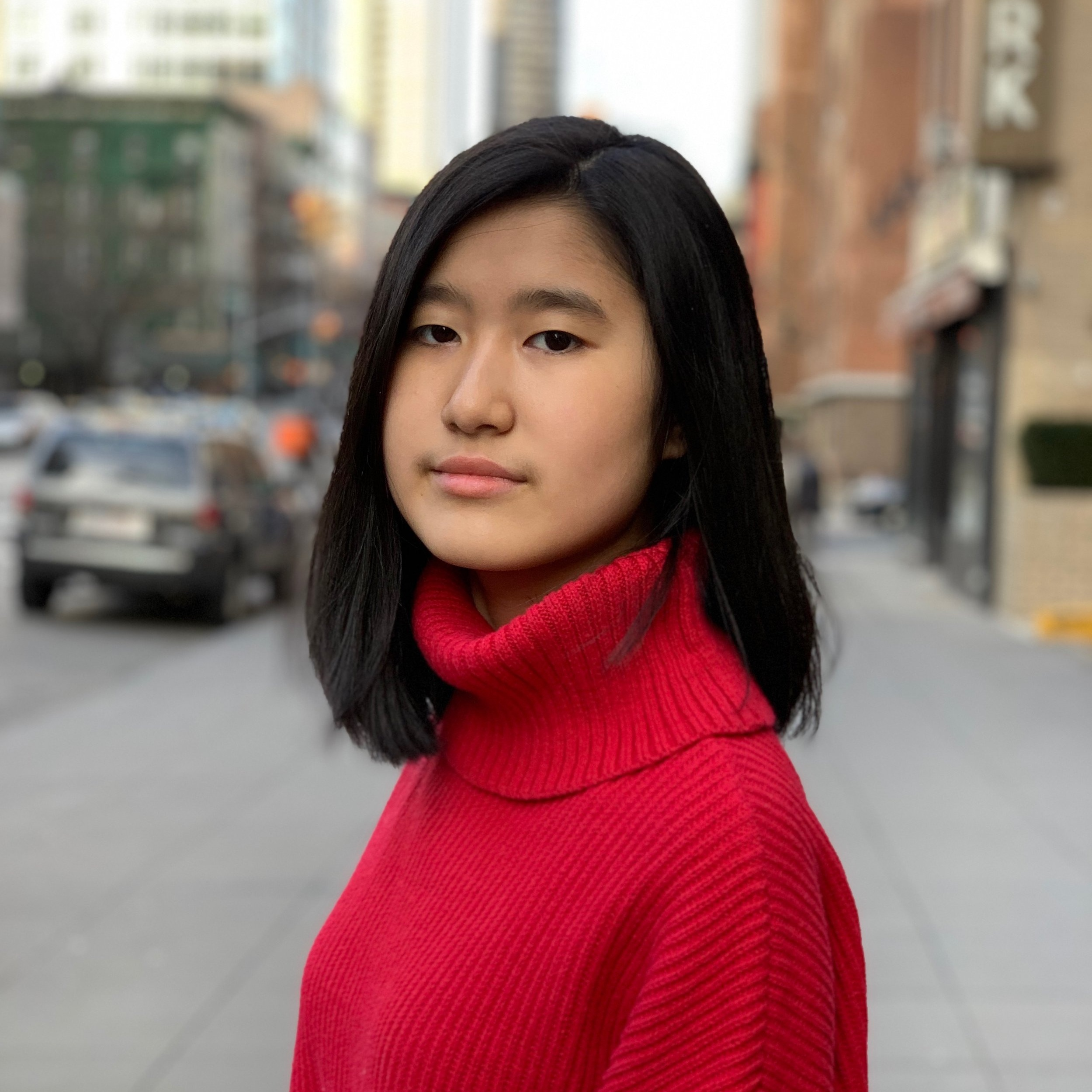 Emma Yang stands outside on a city street, looking at the camera. She has medium length black hair and is wearing a red turtle neck.