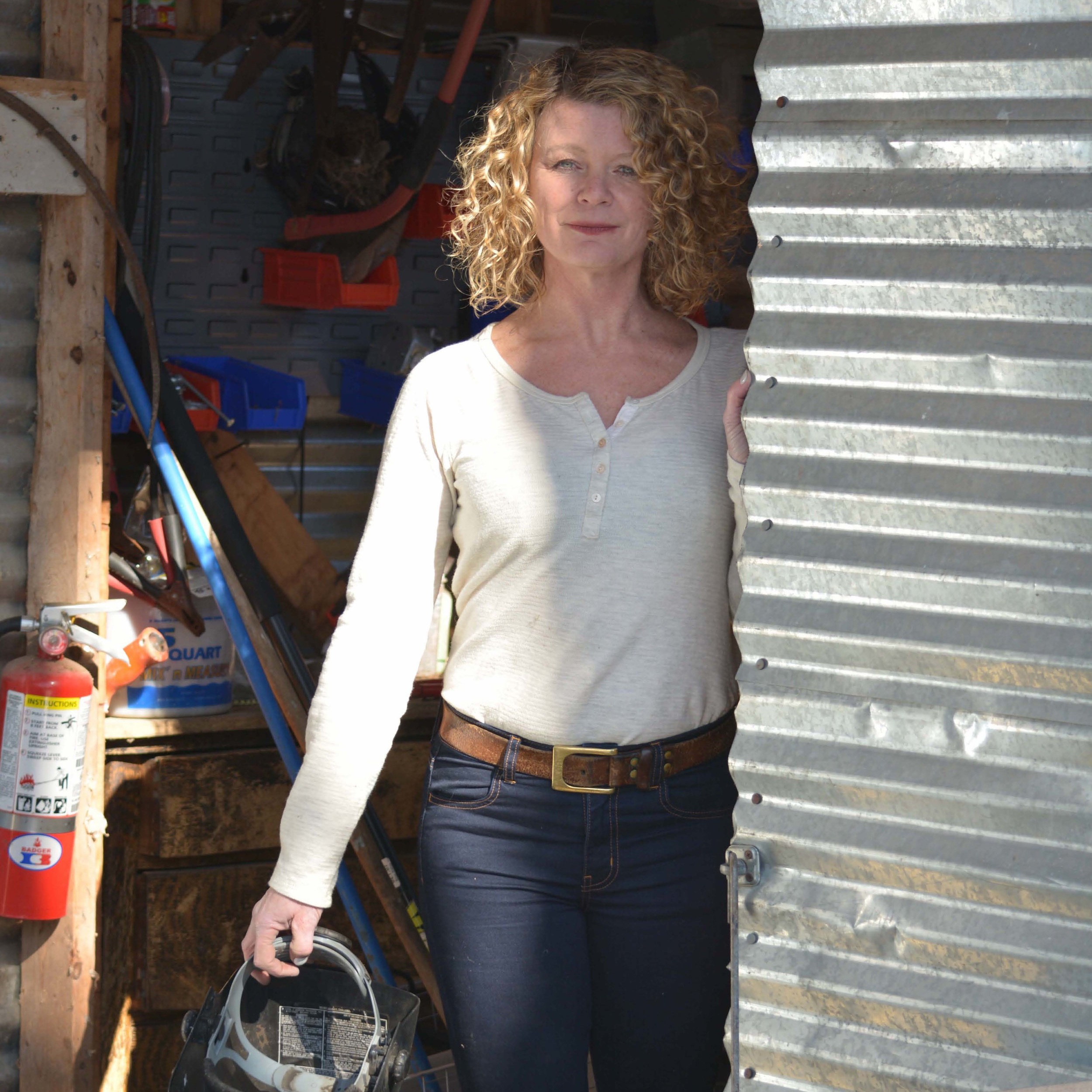 Evelyn Tickle stands smiling at the camera next to a corrugated tin wall. She has shoulder length, curly blonde hair and is wearing jeans and a cream, long sleeve t-shirt.