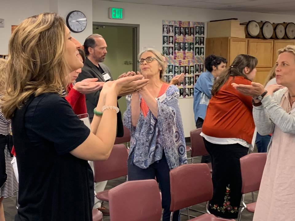 Linda blowing pretend bubbles—a great way to help students become more mindful of breathing at piano lessons.