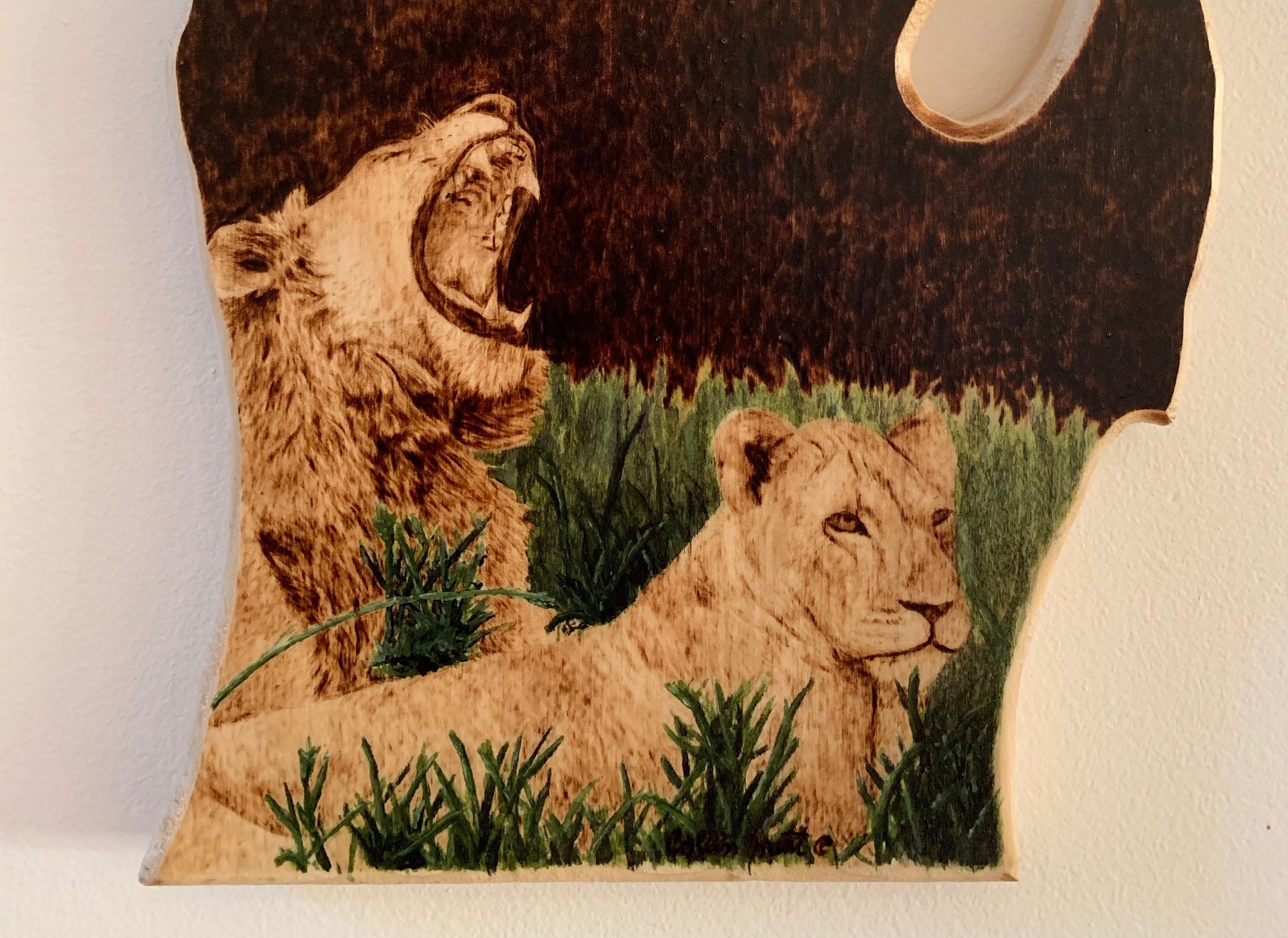 A custom piece for a friend, it entails a wood burned lion and lioness complimented by watercolor on oak.