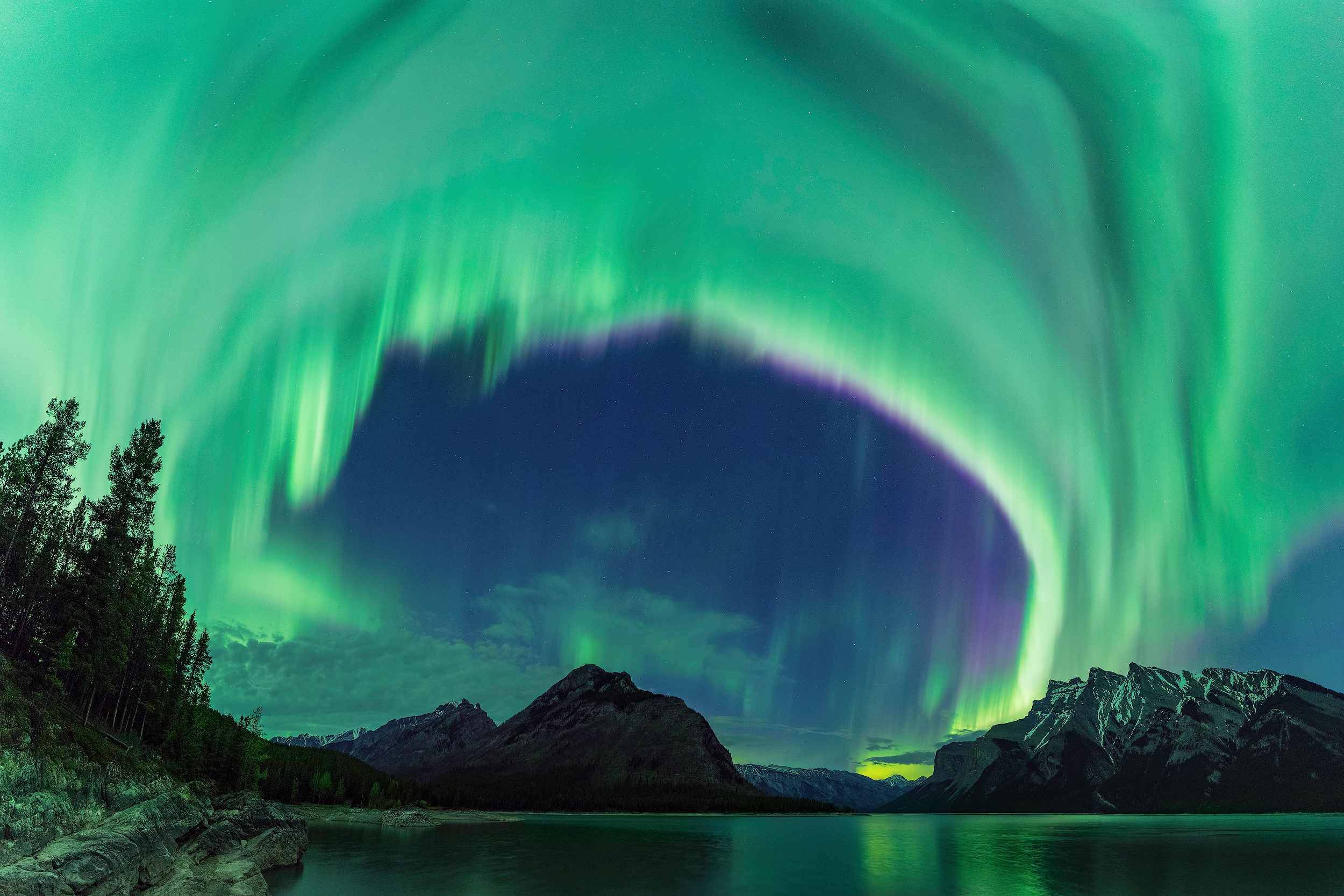 An arching wave of northern lights dances above Lake Minnewanka in Alberta, Canada - Mike Mezeul II – (2500x1667)