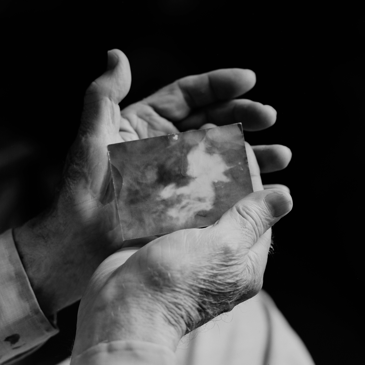 "13. Robert Shatzel Holding Photograph of Baby Leprechaun. Lily Dale. 1996. Toned Gelatin Silver Print. 15""X15""."