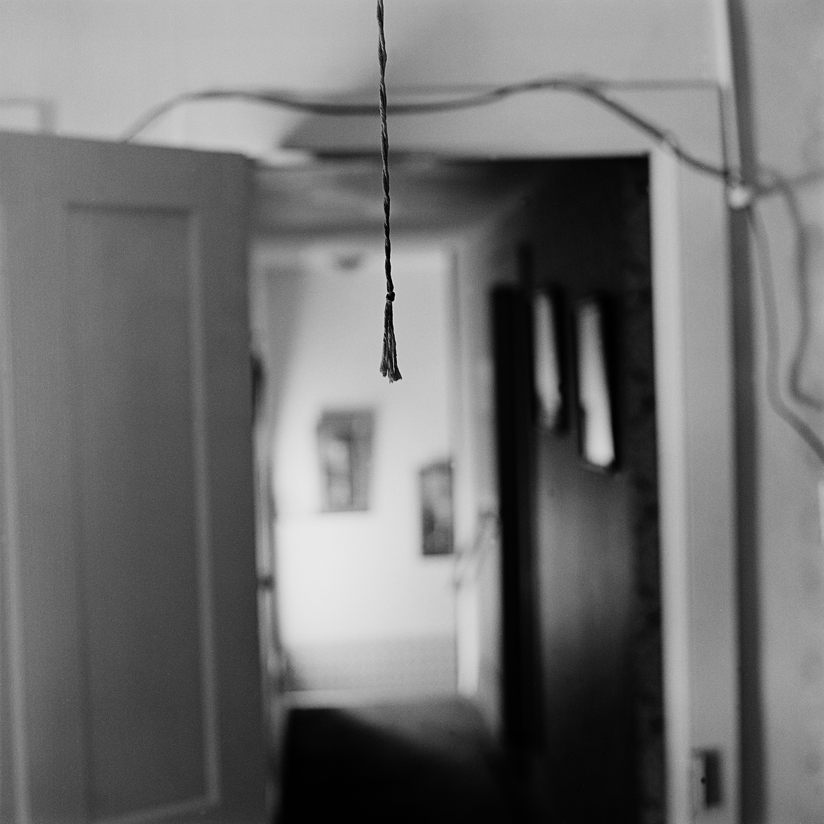 """30. Pullcord, Lewis Apartment, Lily Dale. 1996. Toned Gelatin Silver Print. 15""""X15""""."""